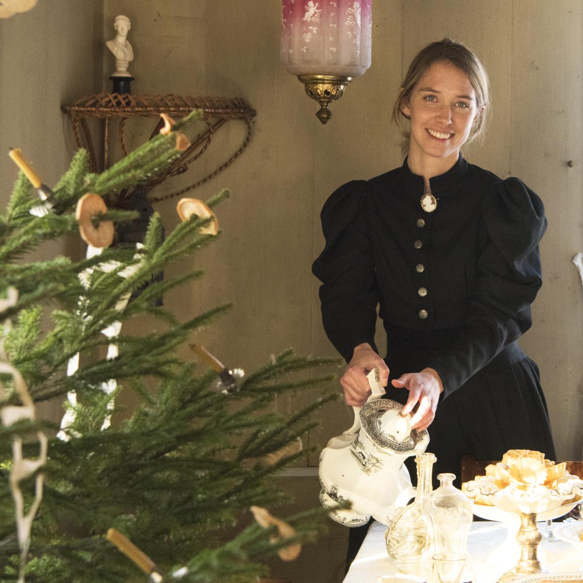 Kvinne skjenker kaffe fra en sølvkanne ved siden av et juletre pyntet med gammeldagse juletrelys i stearin og tørkede epler.