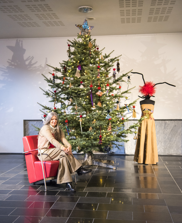 Julie Skarland i en stol foran et juletre pyntet med små Angelina-figurer og en stor Angelina-figur ved siden av.