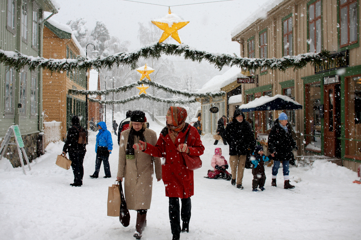 Julegaten på Maihaugen med handlende mennesker, girlandere og snøvær.