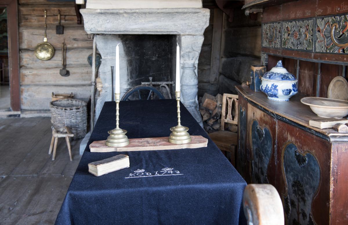 Kiste dekket med et svart teppe står framme i tømmerstua. På teppet ligger en salmebok og en fjøl med utskjæringer med messinglysestaker på.