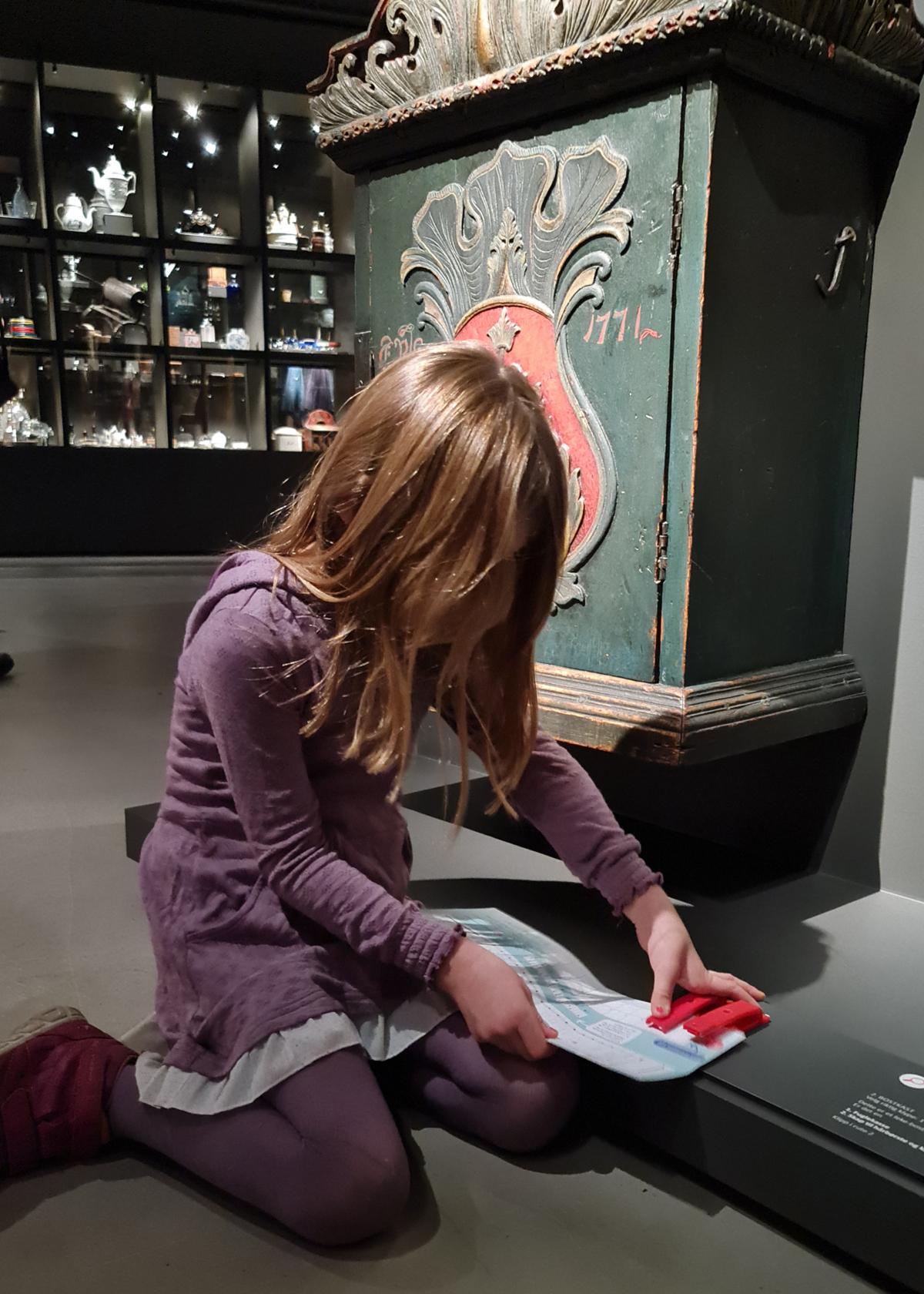 Jente stempler i en brosjyre i utstillingen Impulser.