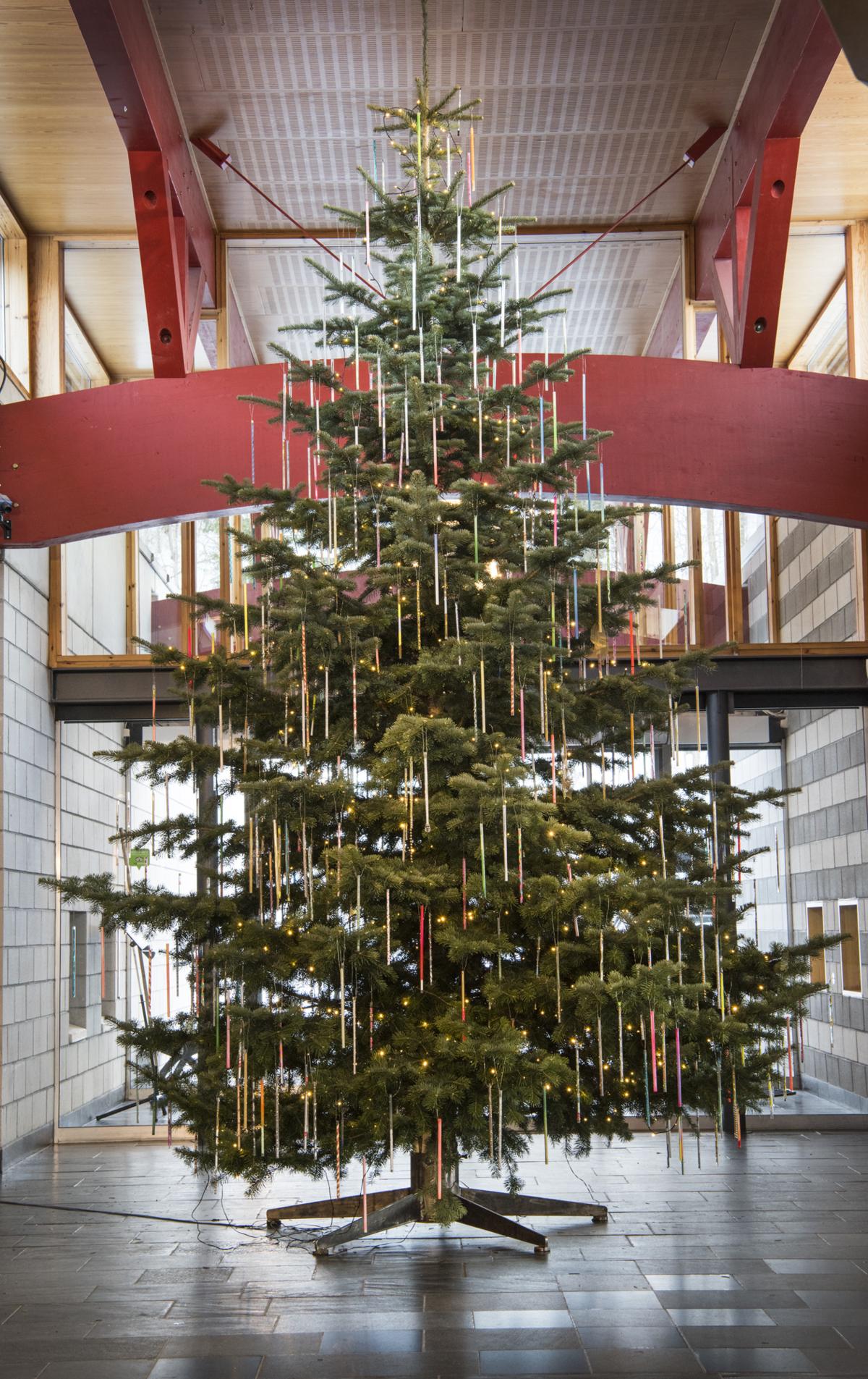 Stort juletre pyntet med lange tynne glassrør i ulike farger.