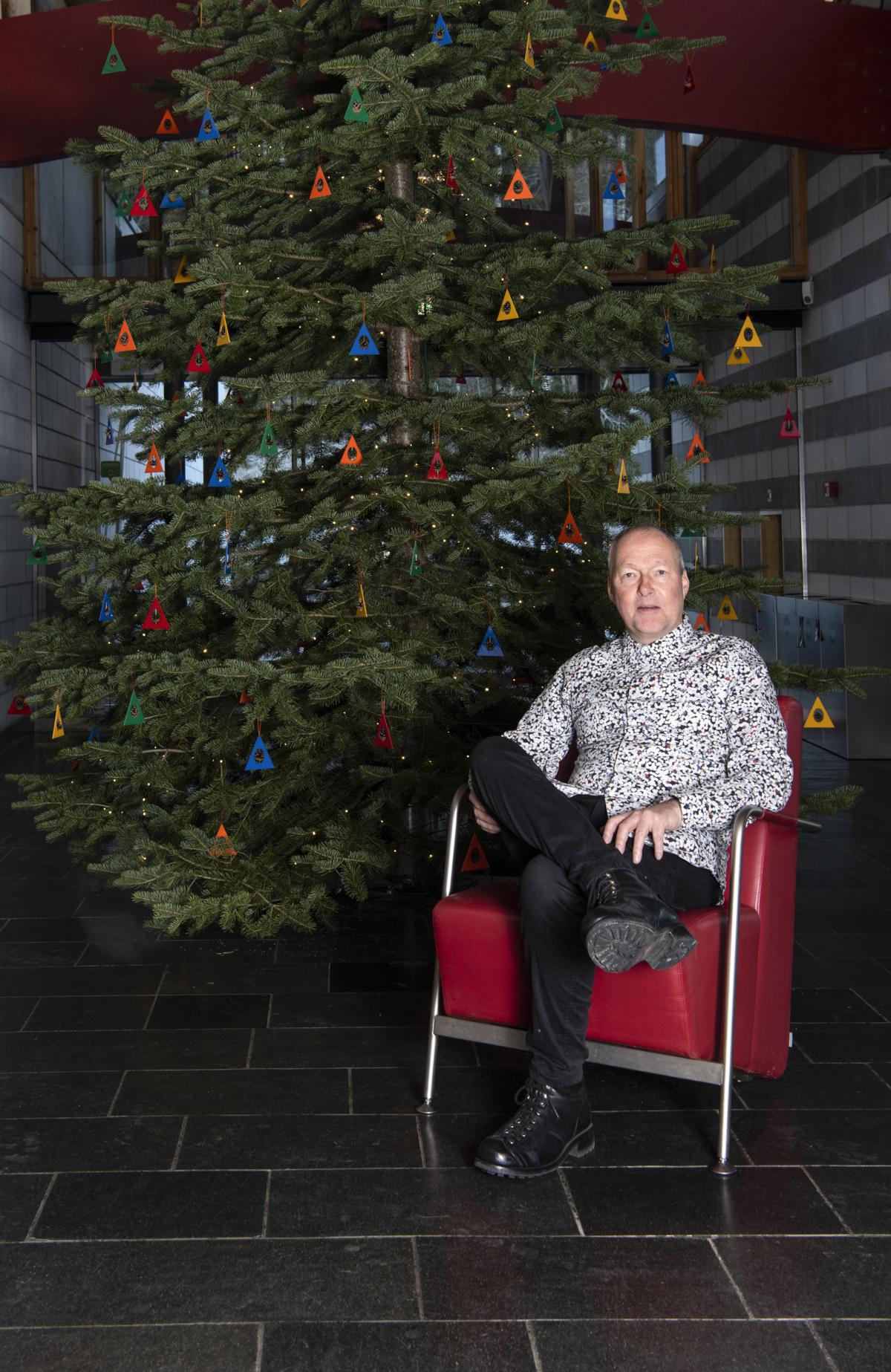 Kunstner Sigurd Bronger sitter i en rød stol foran juletre med fargerike trekanter med kongler.