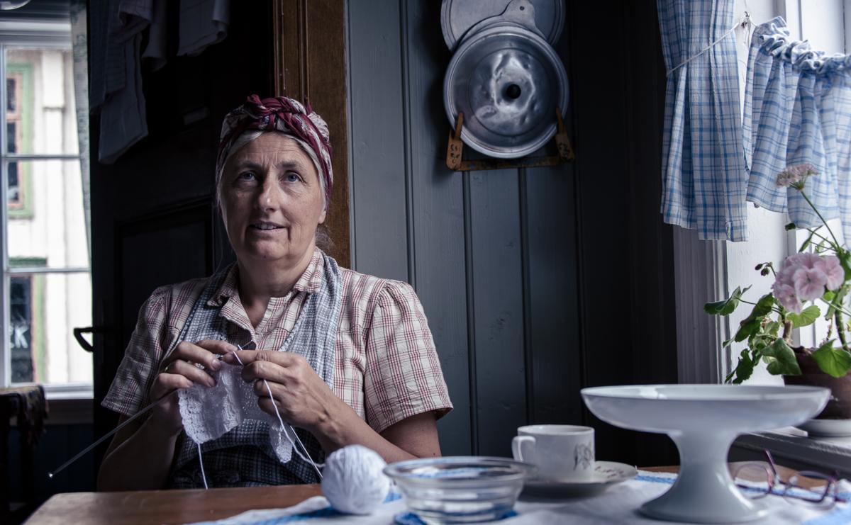 gammel dame sitter ved kjøkken bordet og strikker