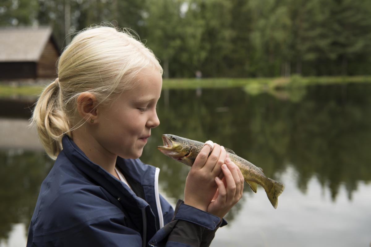 Jente holder en fisk mot ansiktet som om hun skal kysse den.