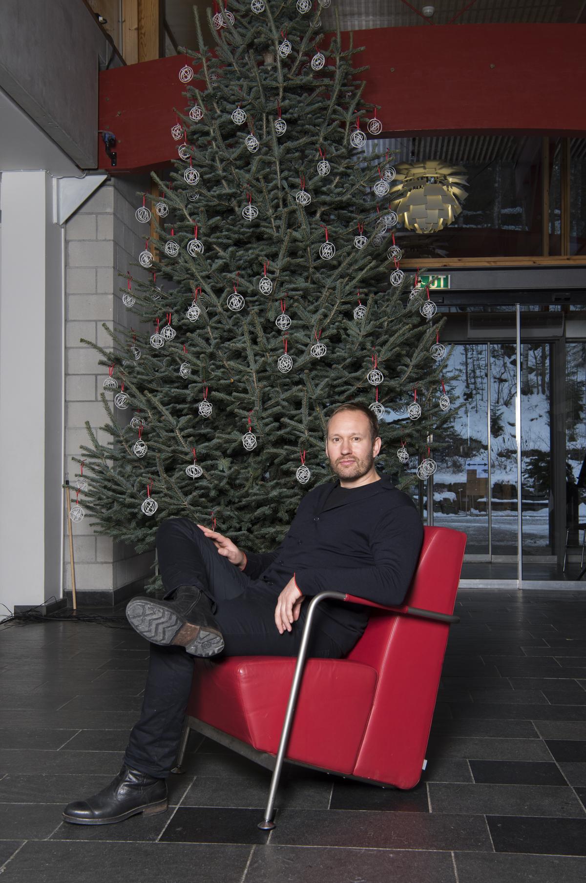 Torbjørn Anderssen sitter foran juletre pyntet med hvite ornamenter.