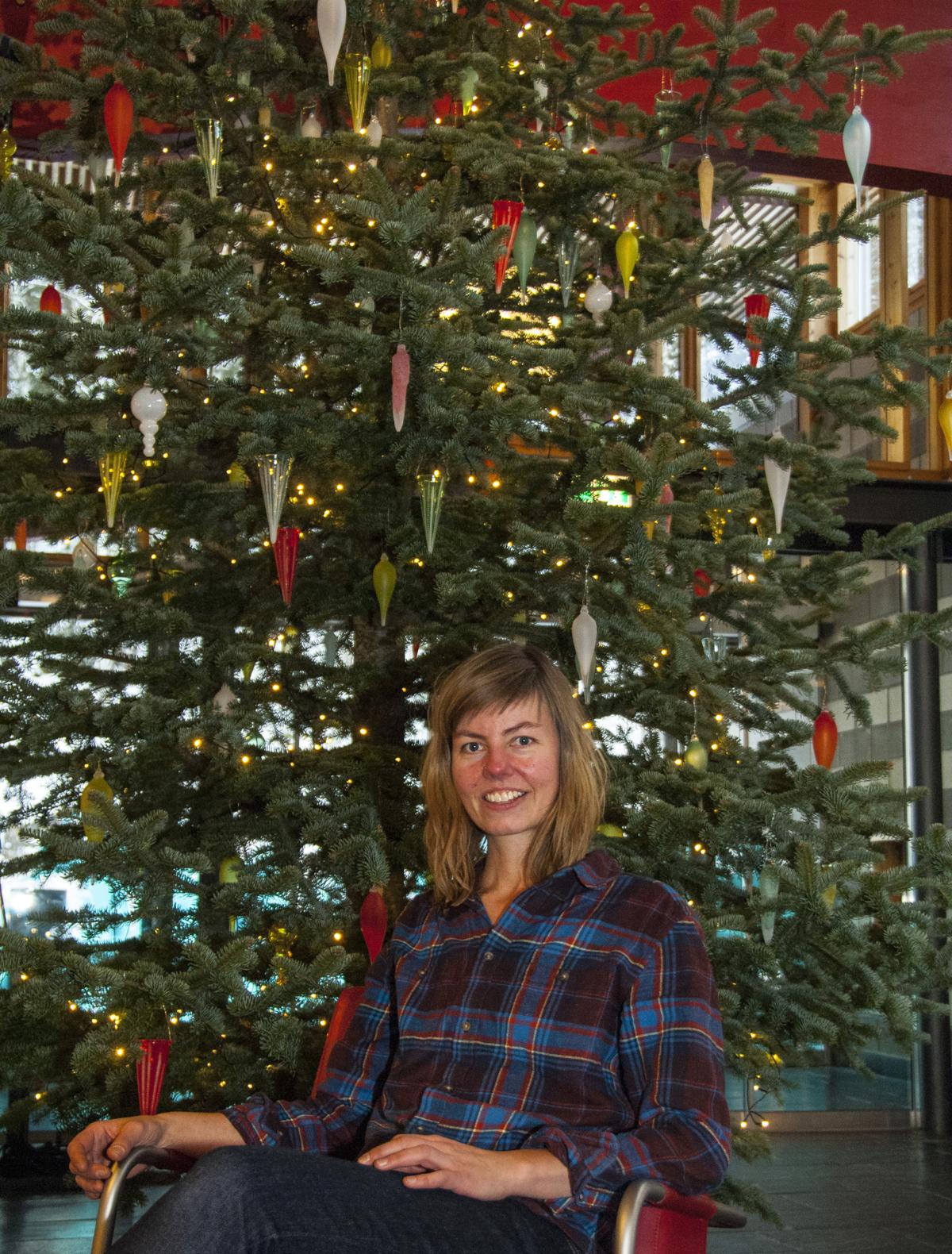 Kari Mølstad foran juletre med glasspynt i ulike farger.