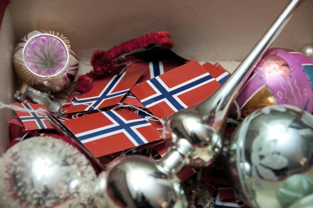 Eske med julekuler, norske flagg og annen juletrepynt fra 1950-tallet.
