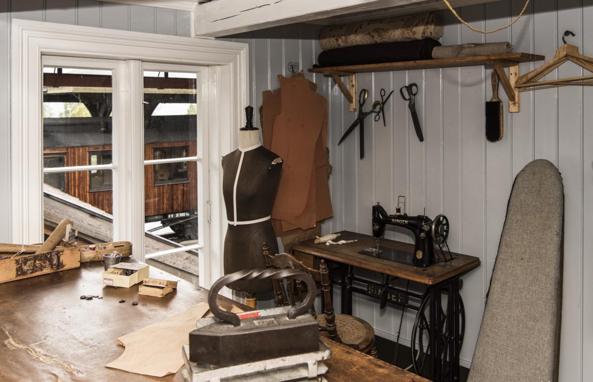 Skredder verksted med historisk utstyr som symaskin, strykejern, sakser og liknende.