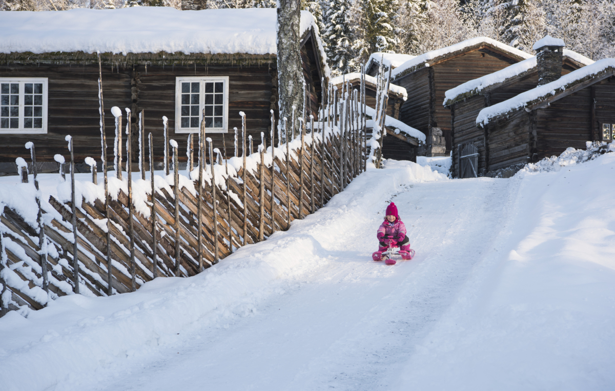 Jente aker ved siden av en skigard og tømmerhus.