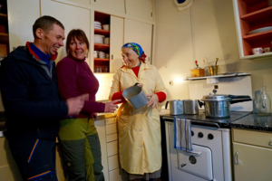 Hushjelpa i 50-tallshuset viser frem datidens kjøkkenredskap.