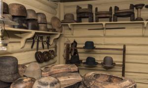 Hattemaker-verksted med sakser, former i tre, annet utstyr og filthatter. I friluftsmuseet Maihaugen på Lillehammer.