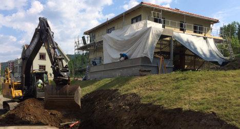 En gravemaskin graver langs skråningen på nedsiden av et gult trehus med stillaser rundt.