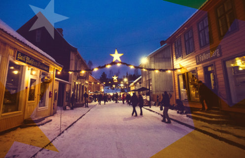 Julegate med granbargirlandere og gule stjerner i historisk bymiljø på Maihaugen.