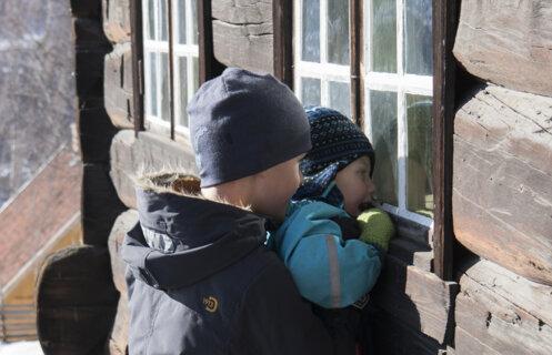 Gutten titter inn gjennom vindu på et tømmerhus.