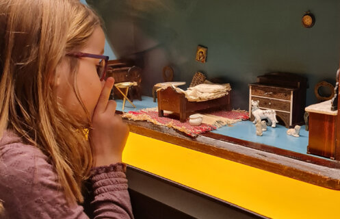 Jente ser på dukkehus i utstilling.