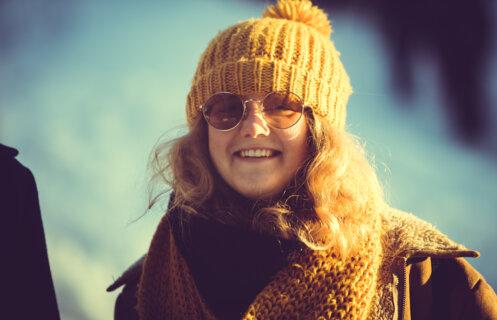 Ung glad kvinne med gul lue og solbriller.