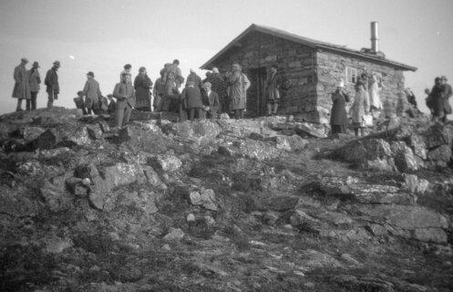 Historisk foto av en steinhytte på fjellet med folk med frakker, hatter og kåper rundt.
