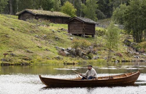 Mann i robåt med fiskestang på vannet foran setergrenda på Maihaugen.