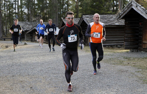 Løpere med startnummer løper forbi historiske tømmerhus på Maihaugen.