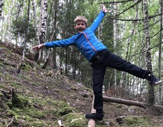 Gutt balanserer på veltet trestamme i skogen.