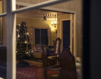 Inn gjennom vinduet til en julepyntet stue i Dronning Sonjas barndomshjem.