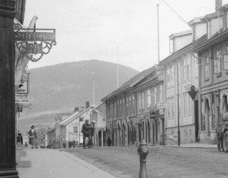 Svart hvitt fotografi av Storgata i Lillehammer med blant annet fasaden til Gullsmed J. Frisenberg. Bildet er fra 1920-1925.