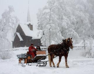Hest og slede foran Garmo stavkirke på Maihaugen en snørik vinterdag.