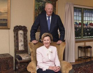 Dronning Sonja sittende i en lenestol med kong Harald stående bak i stuen i dronningens barndomshjem på Maihaugen.