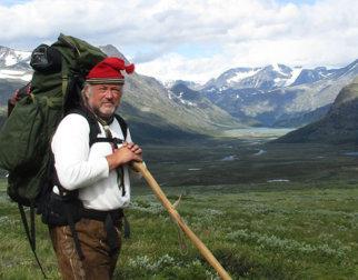 Moderne bilde av mann med gammeldagse klær og stor sekk i fjellheimen.