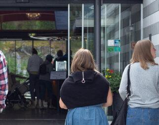 Tre personer på vei inn hovedinngangen på Maihaugen.