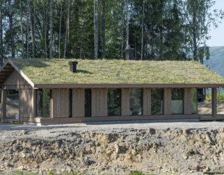 Langstrakt hytte med stående panel og torvtak i friluftsmuseet Maihaugen på Lillehammer.