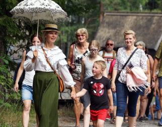 En engelsk fin lady i historiske klær og med paraply leder an et følge med publikummere.