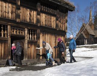 Familie på vei inn i et tømmerhus på Maihaugen.