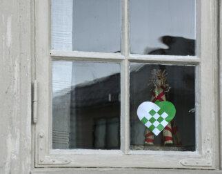 Vindu med julepynt: Halmbukk og juletrekurv.