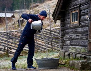 Vann hentes fra brønnen og tømmes i kar. Foto: Esben Haakenstad