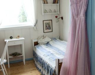 Soverom malt i hvitt og blått, med hvitmalte møbler.
