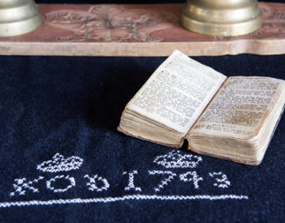 Gammel salmebok ligger på et teppe brodert KOD 1743 og to kroner med korssting. Bak ligger en utskåret trefjøl med to messing lysestaker.