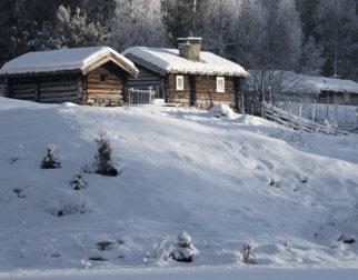 Laftede seterbygninger med snø på taket i vinterlandskap på Maihaugen.