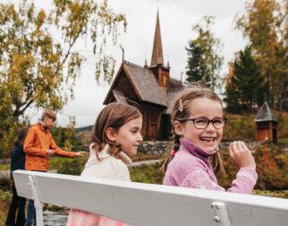 Glade barn mater ender foran Garmo stavkirke på Maihaugen.