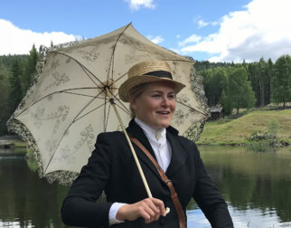 Fin dame med hatt og blondeparaply foran setergrenda på Maihaugen.