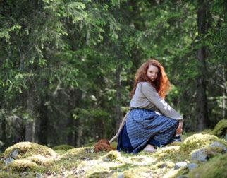 Hulder med gammeldagse klær, flott hår og hale sitter på mosen i skogen.