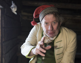 Morten Jostad med hvit vadmelsjakke, grønn vest og rød stikket lue.