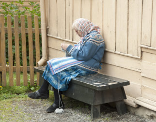 Frivillig sitter og strikker på Maihaugen.