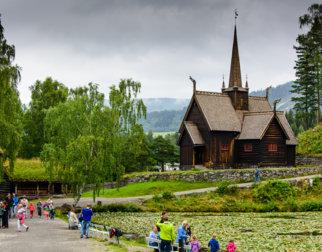 Garmo stavkirke på Maihaugen, med tjernet og besøkende foran.