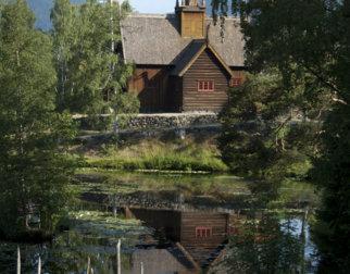 Garmo stavkirke speiler seg i tjernet på Maihaugen.