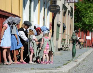 Barn utkledd i klær fra gamledager flokker seg rundt en ung mann i gammeldags kostyme i hovedgata i Byen på Maihaugen.
