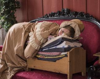 """Dami i gammeldags kjole og kyse ligger oppå en liten seng med mange madrasser slik som i eventyret """"Prinsessen på erten""""."""