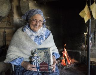 Koselig dame med skaut og gammeldagse klær sitter foran peisen med en eventyrbok og en filledukke.