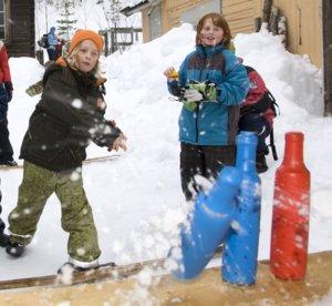 Barn kaster snøball på flasker